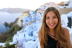 Portrait of smiling girl in Oia village, Santorini. Cute happy tourist girl taking picture during summer vacation in famous stock photography