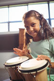 Portrait of smiling girl playing bongo drums stock photos
