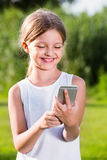 Portrait of smiling girl playing with mobile phone Stock Photos