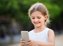 Portrait of smiling girl playing with mobile phone Royalty Free Stock Photo