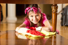 Portrait of smiling girl polishing wooden table with cloth Royalty Free Stock Photo