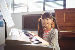 Portrait of smiling girl practicing piano Royalty Free Stock Images