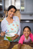 Portrait of smiling girl preparing food with mother at home Royalty Free Stock Image