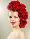 Portrait of smiling girl with red roses hairstyle Royalty Free Stock Photography