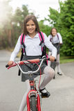 Portrait of smiling girl in school uniform riding bicycle Stock Photos