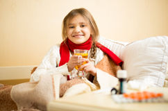 Portrait of smiling girl sitting in bed and drinking hot tea Royalty Free Stock Photo