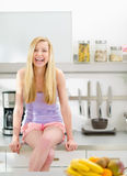 Portrait of smiling girl sitting in kitchen Royalty Free Stock Photos