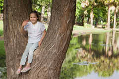 Portrait of a smiling girl sitting on tree at park Stock Photo