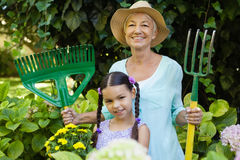 Portrait of smiling girl standing with grandmother holding gardening equipment. At backyard Stock Image