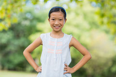 Portrait of smiling girl standing with hand on hip. In the park Stock Image