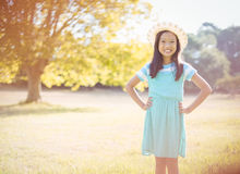 Portrait of smiling girl standing with hand on hip in park Stock Image