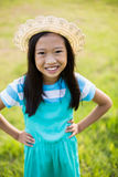 Portrait of smiling girl standing with hand on hip in park. On a sunny day Royalty Free Stock Image