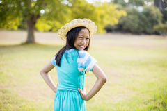 Portrait of smiling girl standing with hand on hip in park. On a sunny day Stock Images