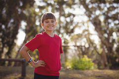 Portrait of smiling girl standing with hands on hip. In boot camp royalty free stock images