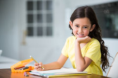 Portrait of smiling girl studying at desk royalty free stock photos