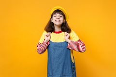 Portrait of smiling girl teenager in french beret, denim sundress clenching fists on chest isolated on yellow wall royalty free stock photography