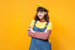 Portrait of smiling girl teenager in french beret and denim sundress holding hands crossed isolated on yellow wall. Background in studio. People sincere royalty free stock photography