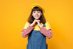 Portrait of smiling girl teenager in french beret, denim sundress holding hands near face isolated on yellow wall. Background in studio. People sincere emotions stock images
