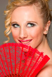 Portrait of smiling girl with textile fan Stock Photos