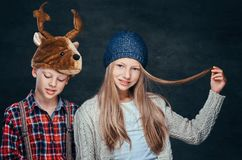 Portrait of a smiling girl in winter hat and cute boy in deer hat. Portrait of a smiling girl in winter hat and cute boy in deer hat on a dark textured stock image