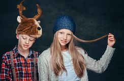 Portrait of a smiling girl in winter hat and cute boy in deer hat. Portrait of a smiling girl in winter hat and cute boy in deer hat on a dark textured royalty free stock images