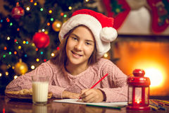 Portrait of smiling girl writing letter to Santa Stock Photos