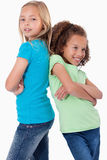 Portrait of smiling girls standing back to back Royalty Free Stock Images