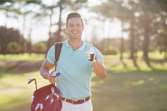 Portrait of smiling golfer man showing thumbs up. While standing on field Stock Photography