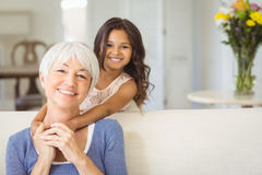 Portrait of smiling granddaughter embracing her grandmother in living room Royalty Free Stock Images