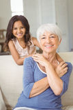 Portrait of smiling granddaughter embracing her grandmother in living room Royalty Free Stock Photo