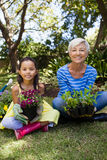 Portrait of smiling granddaughter and grandmother holding plants sitting with crossed legs. At backyard Stock Photo