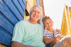 Portrait of smiling grandfather and boy sitting at beach hut. On sunny day Stock Photography