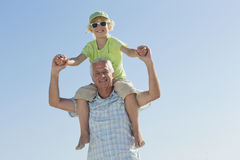 Portrait of smiling grandfather carrying grandson on shoulders against blue sky Stock Photos