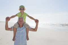 Portrait of smiling grandfather carrying grandson on shoulders on sunny beach Stock Images