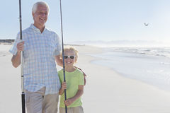 Portrait of smiling grandfather and grandson with fishing rods on sunny beach Stock Image