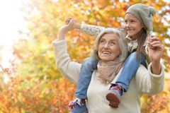 Smiling grandmother and granddaughter. Portrait of smiling grandmother and granddaughter  outdoors Stock Photo