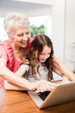 Portrait of smiling grandmother and granddaughter using laptop Royalty Free Stock Photos