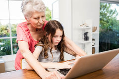 Portrait of smiling grandmother and granddaughter using laptop Stock Photography