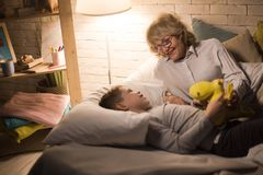 Grandmother Telling Stories to Little Boy. Portrait of smiling grandmother laying in bed with little grandson and telling him bedtime stories Royalty Free Stock Photo