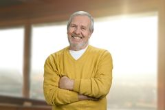 Portrait of smiling grandpa at home. Cheerful old man in yellow sweater with crossed folded arms against windows background indoor stock photo