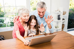 Portrait of smiling grandparents and granddaughter using laptop Royalty Free Stock Photo