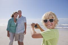 Portrait of smiling grandson with digital camera photographing grandparents on sunny beach Royalty Free Stock Photography