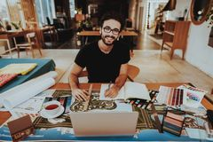 Portrait of Smiling Graphic Designer Enjoys Work. Handsome Caucasian Bearded Illustrator Looking at Camera Sits at Table Doing Creative Project at Workplace stock image