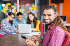 Portrait of smiling graphic designer using digital tablet while colleagues working in background Stock Image
