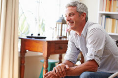 Portrait of�a smiling grey haired man sitting in a room Royalty Free Stock Photos