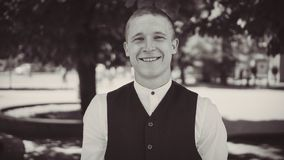 Portrait of a smiling groom in a black vest stock image