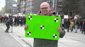 Portrait of Smiling guy who agitates by propaganda with a green poster 4k. Revolution in city during day. Protesters Crowd people stock video