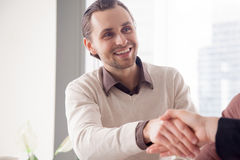 Portrait of smiling handsome businessman shaking female hand on stock photography