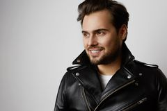 Portrait of smiling handsome fashion model in leather jacket resting while standing on white background. Horizontal. royalty free stock image