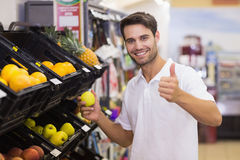Portrait of a smiling handsome man buying a fruit with thumb up Stock Photos